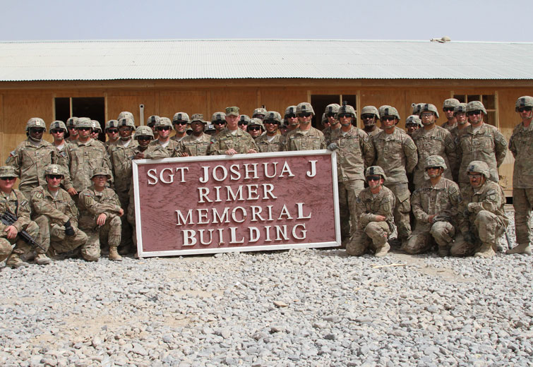 KANDAHAR AIR FIELD, Afghanistan – Command Sgt. Maj. Ronnie Kelley, U.S. Army Central, stands with Soldiers of the 687th Horizontal Engineer Company, 315th Engineer Battalion, 45TH CENTCOM Material Recovery Element, July 26, 2014, in front of a building dedicated to Sgt. Joshua J. Rimer, an engineer who died July 22, 2009 while serving during Operation Enduring Freedom. Kelley thanked Soldiers for their hard work and dedication to the unit's mission. (U.S. Army photo by Sgt. Tracy R. Myers, U.S. Army Central)