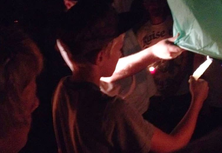 James Camp V illuminates a lantern for his father / photo submitted by Terry Griffith
